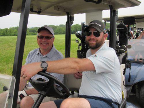 Golfers in golf cart at MIB golf event