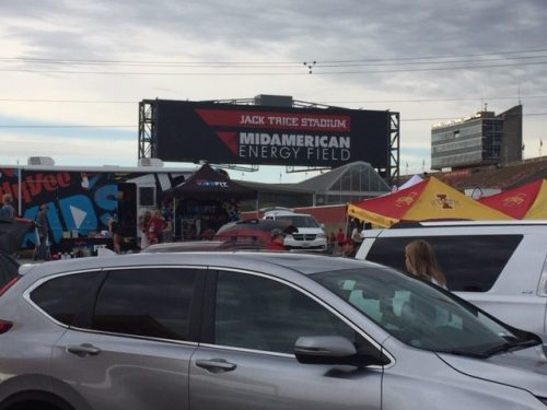 parking lot full of cars and tents at tailgate event